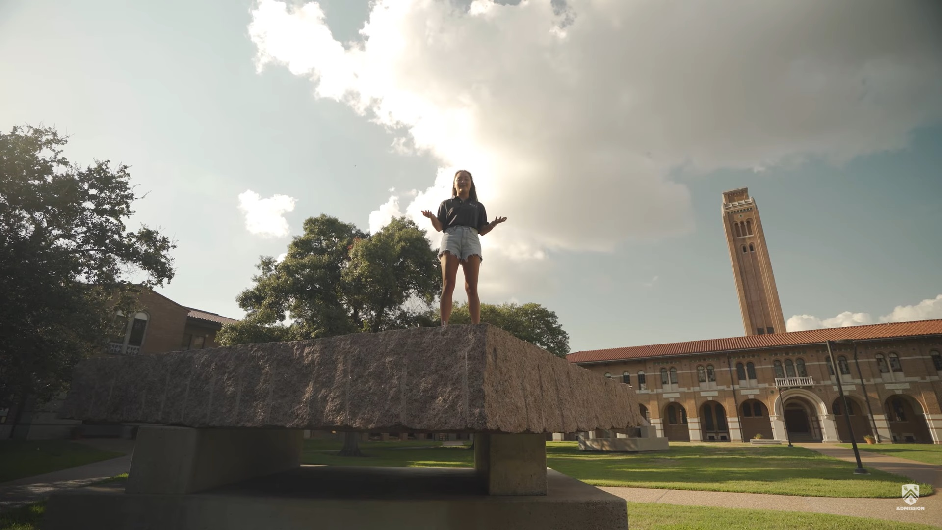 The tour guide stands on top of a large slab of concrete in the Engineering Quad, which is one part of the public art piece that sits in the quad.