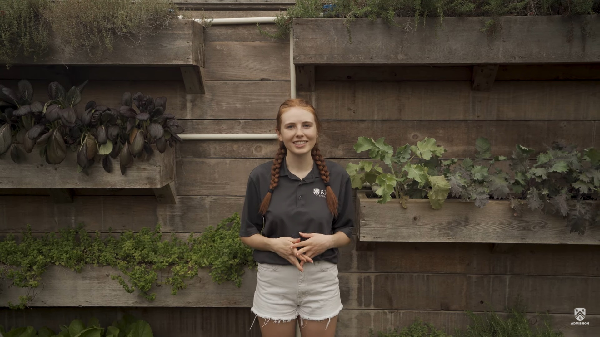 Student stands in front of planters located in the Betty and Jacob Friedman Holistic garden.