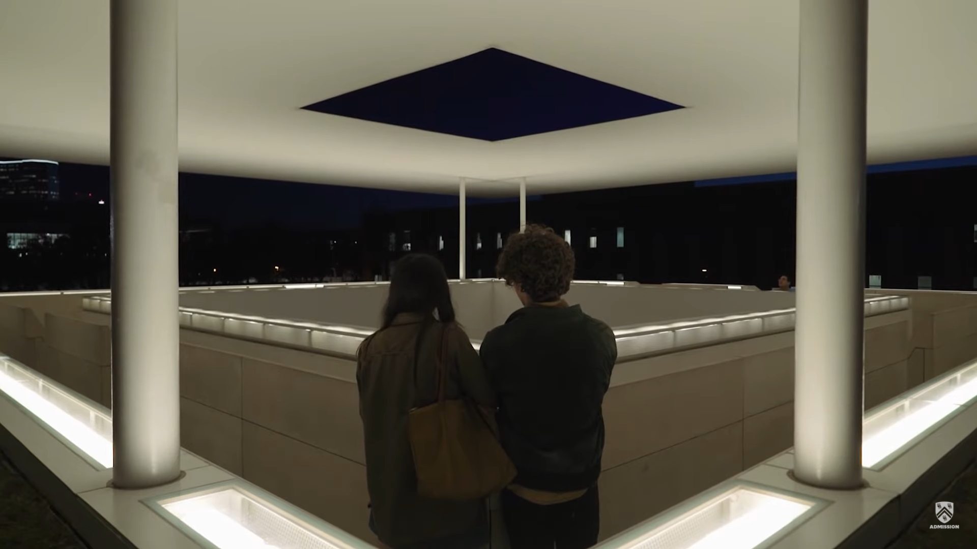 Two people stand inside a corner of the upper level of the Skyspace, which has a square walkway around a square open space.