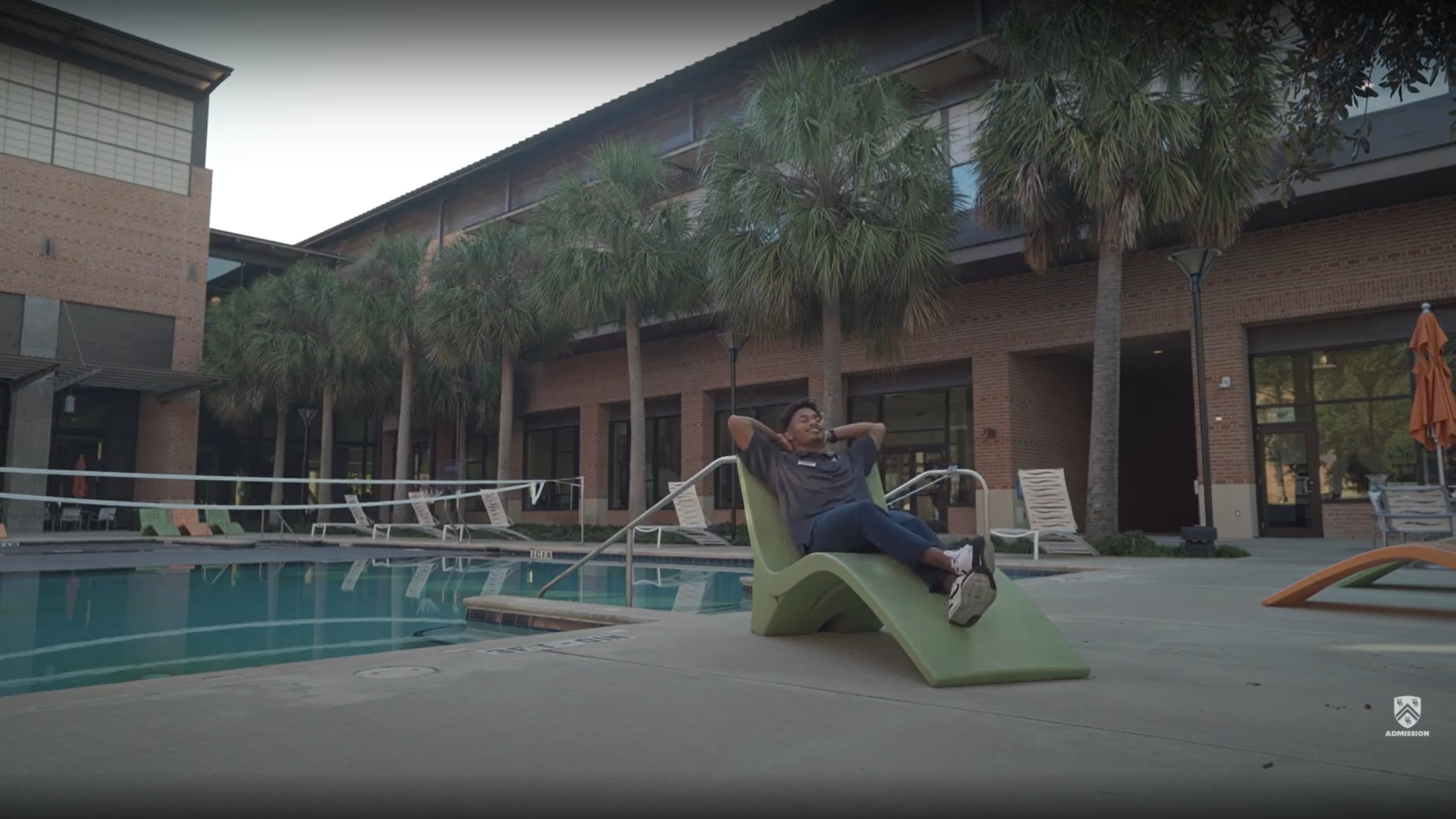 Tour guide relaxes on a lounge chair next to the recreation pool at the Rice Aquatics Center.