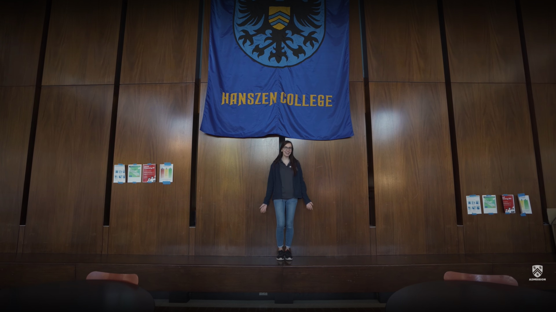 """Student stands inside of the Hanszen College commons in front of a large blue banner that reads """"Hanszen College."""""""