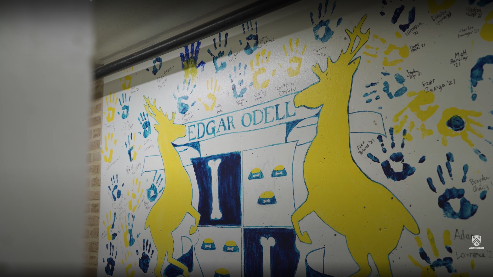 A picture of a painted mural inside of Lovett College featuring their college crest and students' handprints.
