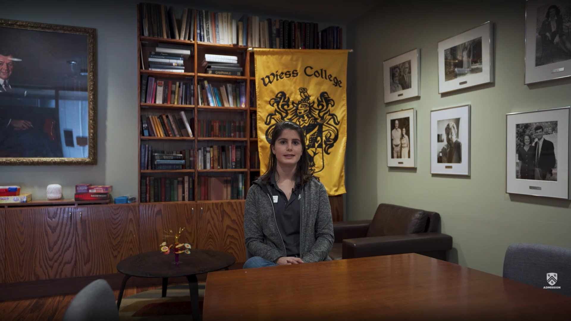 A student sits in a nook inside of Wiess College in front of their college flag.