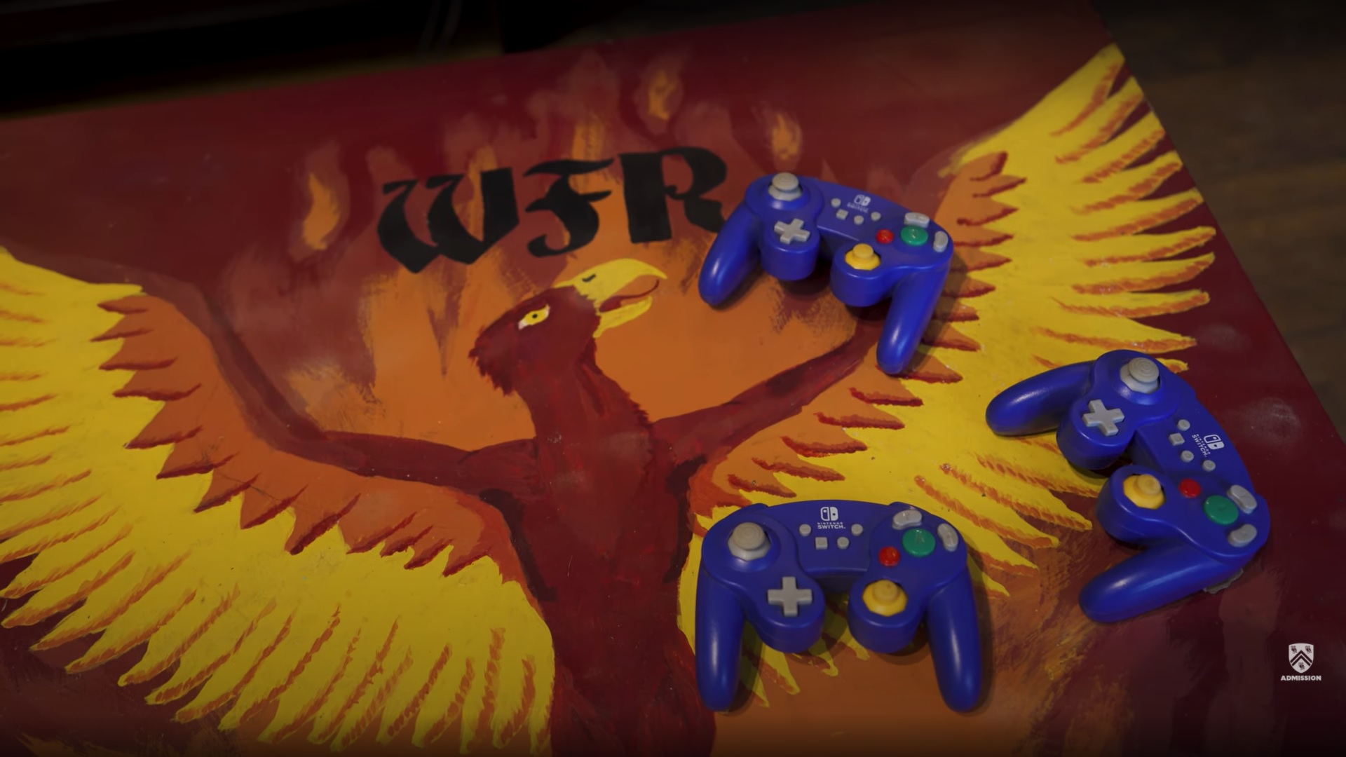 Three blue game controllers sit on top of a table painted with the mascot of Will Rice College, a phoenix.