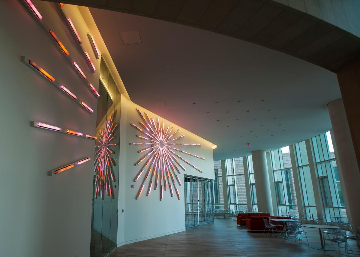 Image inside a lobby in the Bioscience Research Collaborative, with tables and chairs as well as a decorative light on the wall.