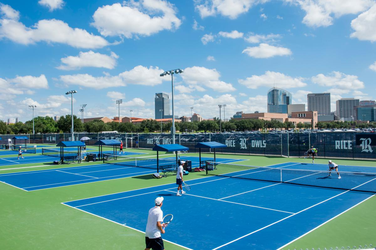 Wide angle picture of tennis courts, with students playing doubles tennis.