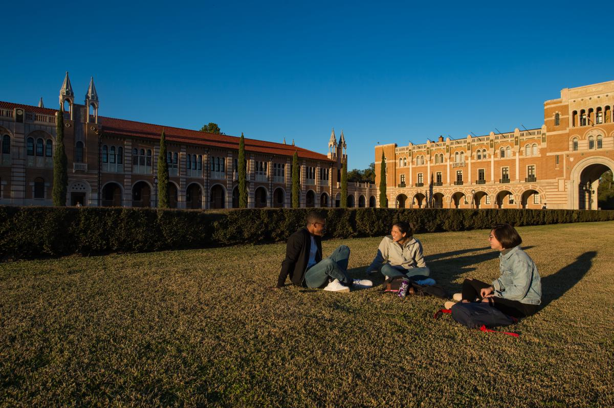 Students sitting on the grass inside the hedges of the academic quad, with Herzstein Hall and Lovett Hall in the background.