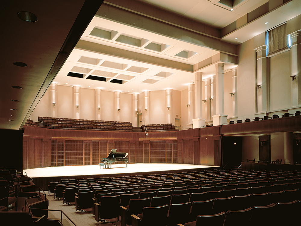 Picture taken from back of concert hall with grand piano in center of stage.