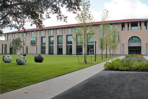 Side view from outside the Anderson-Clarke Center that includes sculpture called In Play. The sculpture is multiple gray spheres scattered across grass courtyard.