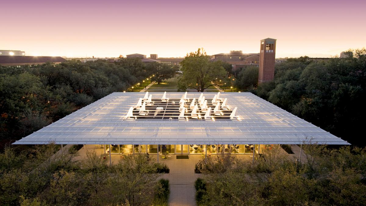 Aerial view of Brochstein Pavilion, showing its large white roof lit up at dusk.
