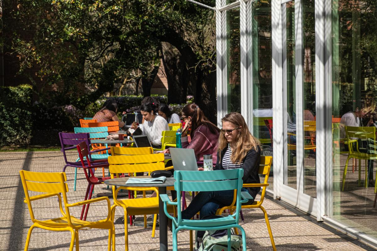 Student sitting on the patio of Brochstein Pavilion which features colorful chairs and tables.