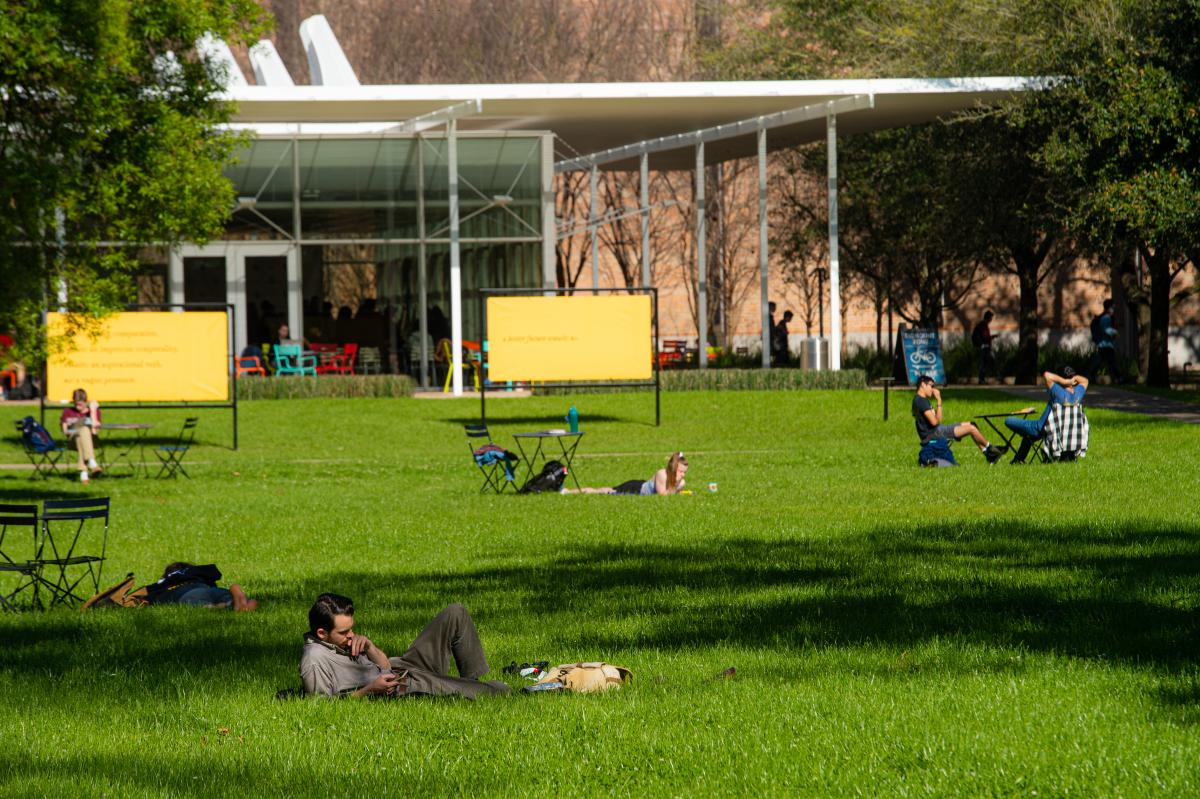 Students lay on the grass in Central Quad, with Brochstein Pavilion in the background.