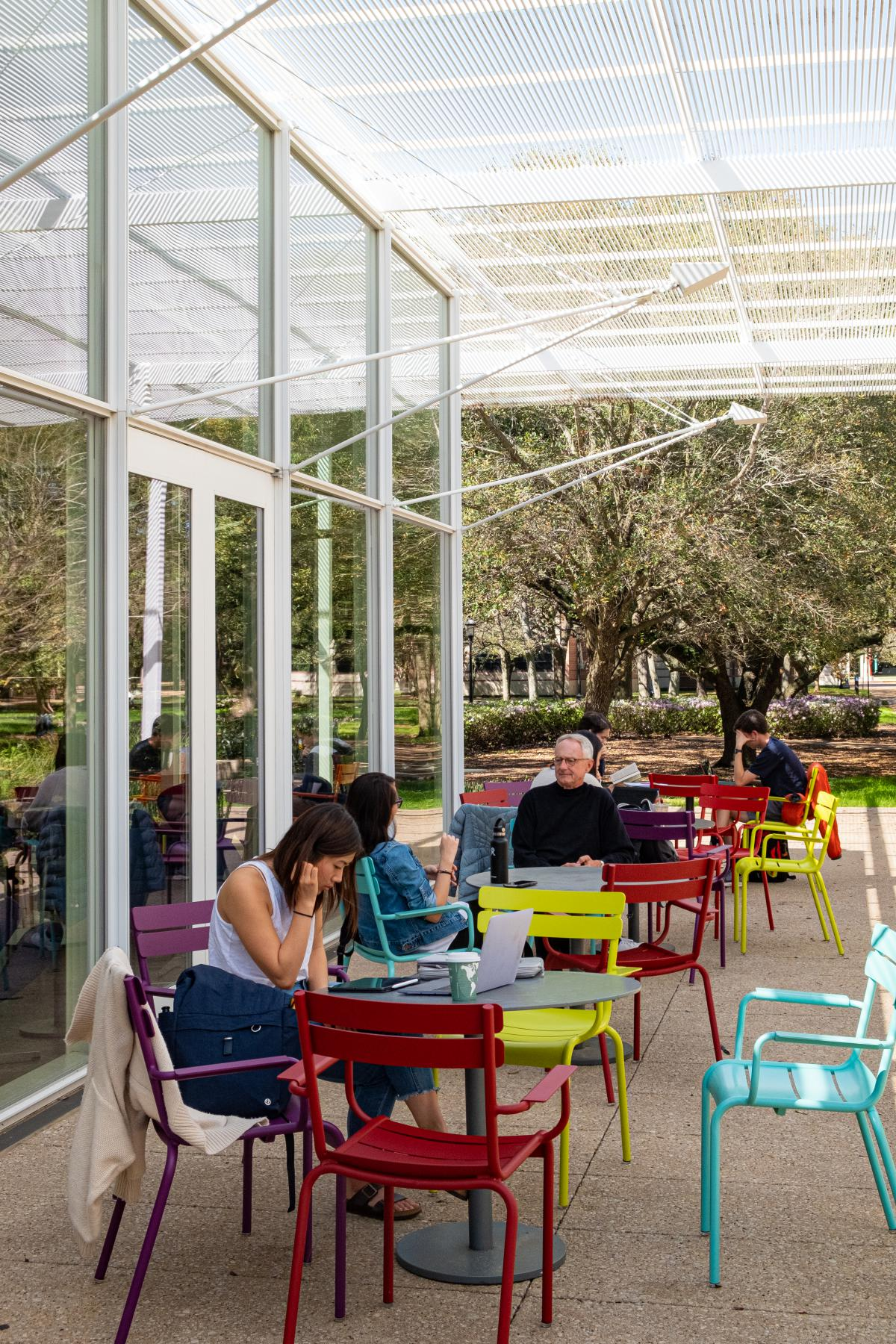 Vertical picture of students sitting on the wrap-around patio of Brochstein Pavilion, which features colorful chairs and tables.