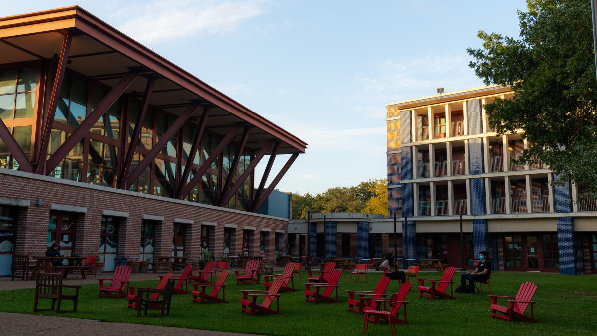 Outside angle view of Brown College and a courtyard full of red lounge chairs.