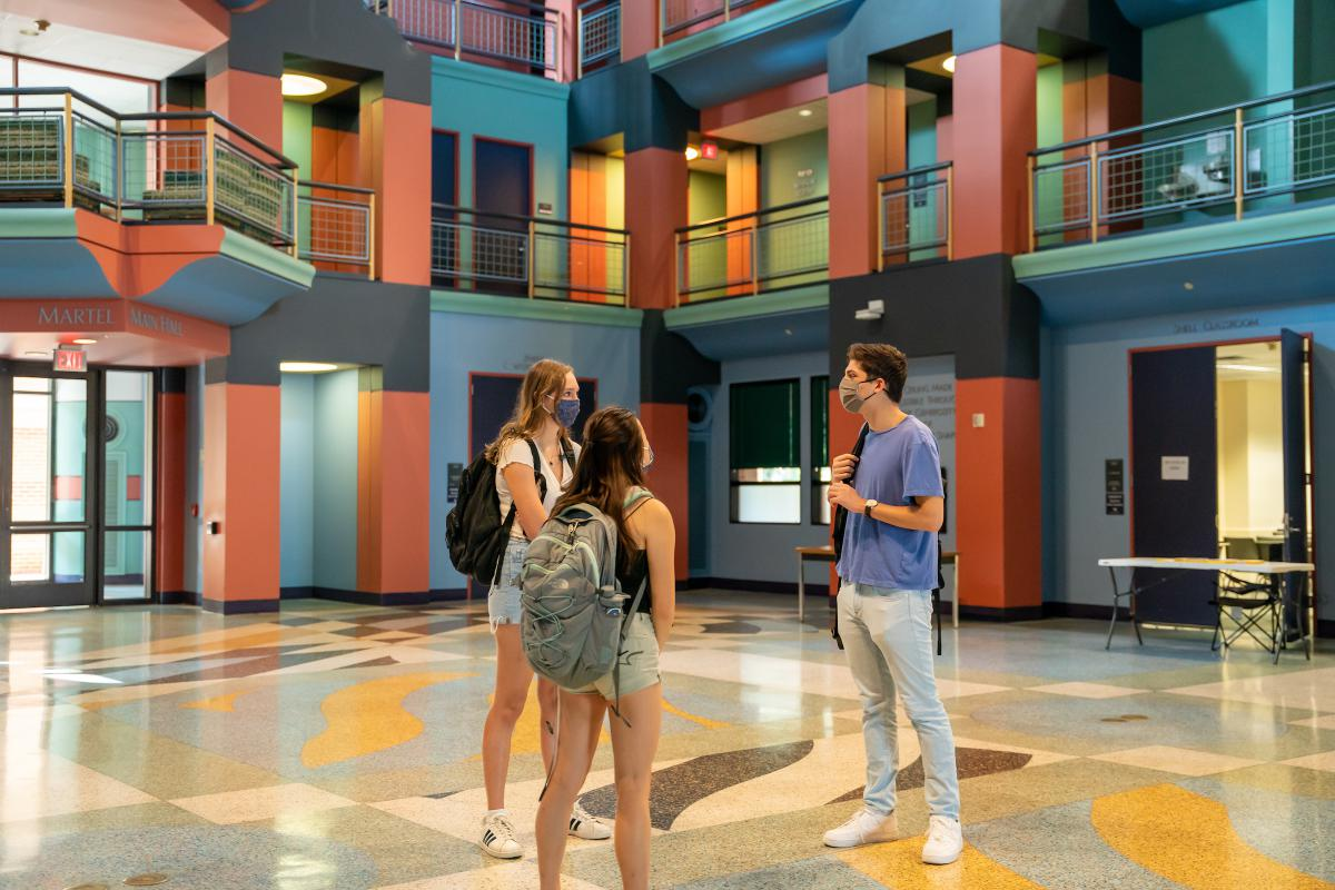 Inside colorful main lobby of Duncan Hall featuring three students in the center facing each other.