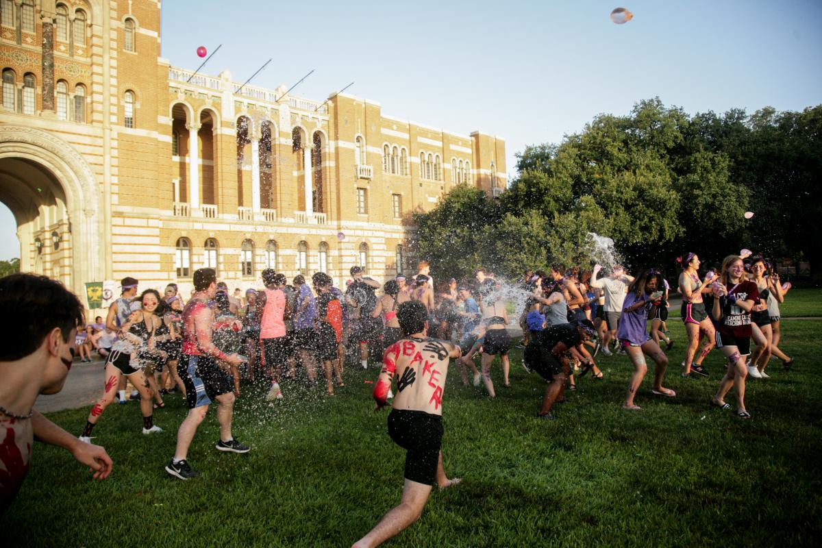 A large group of students are throwing water balloons at each other in the grassy courtyard in front of Lovett Hall.