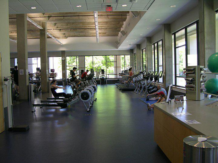Inside picture of the main workout room inside the Gibbs Recreation Center. Exercise equipment shown includes elliptical machines, treadmills and stationary bikes.