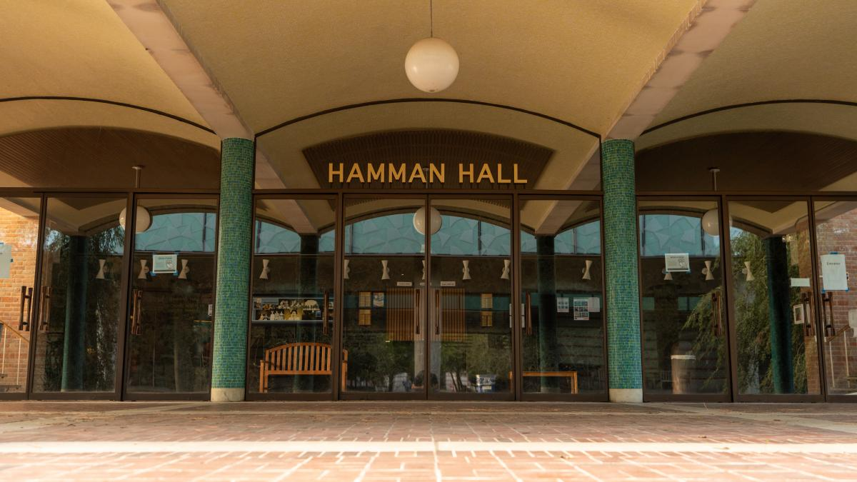 Picture of the front doors to Hamman Hall, with the name written on the glass.