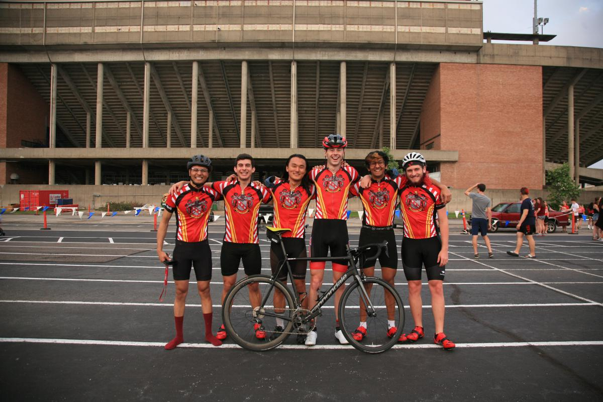 A group of 6 students in biking gear stand behind a bike at the Bike Track.