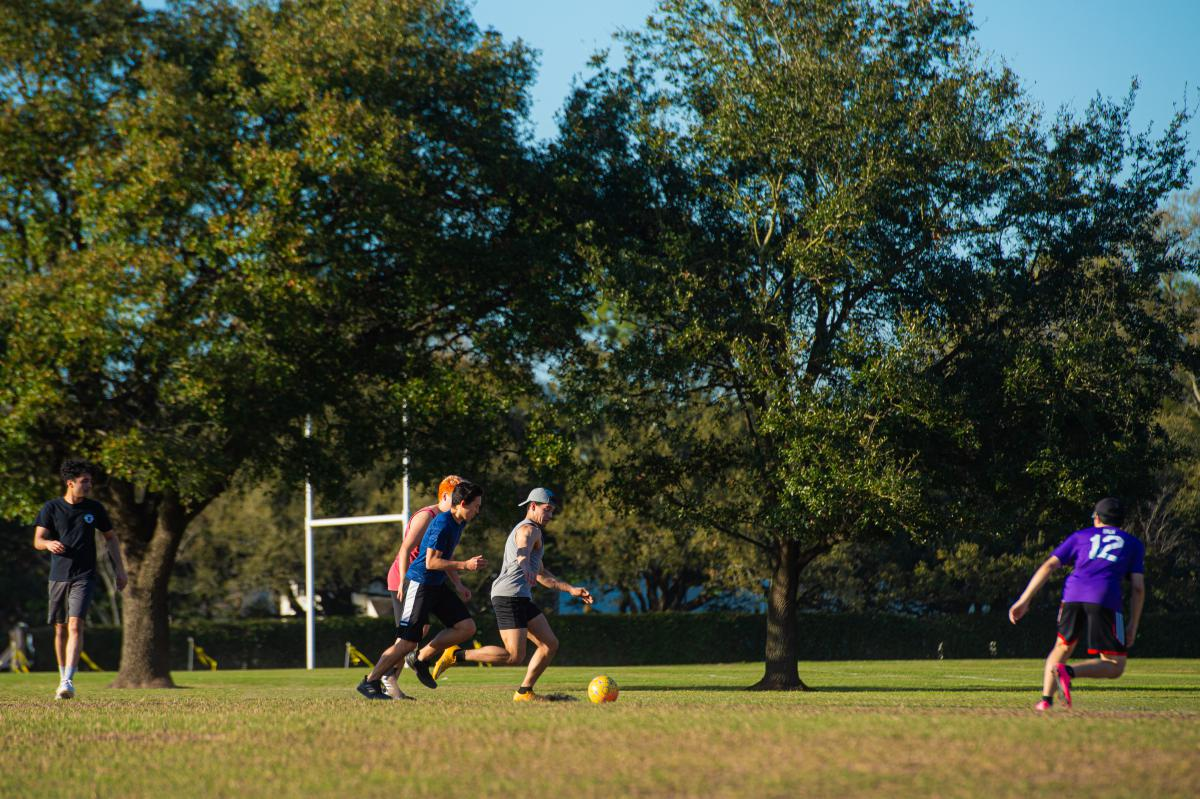 Students playing soccer on a soccer field.