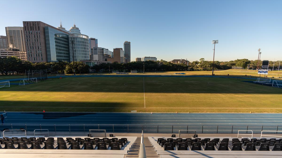 Picture of the track and soccer field taken from the stands, with the Texas Medical Center in the background.