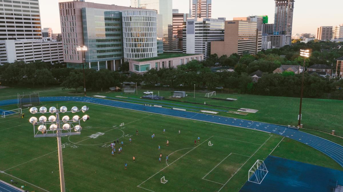 Aerial view of soccer field with students playing and buildings in the Texas Medical Center in the background.