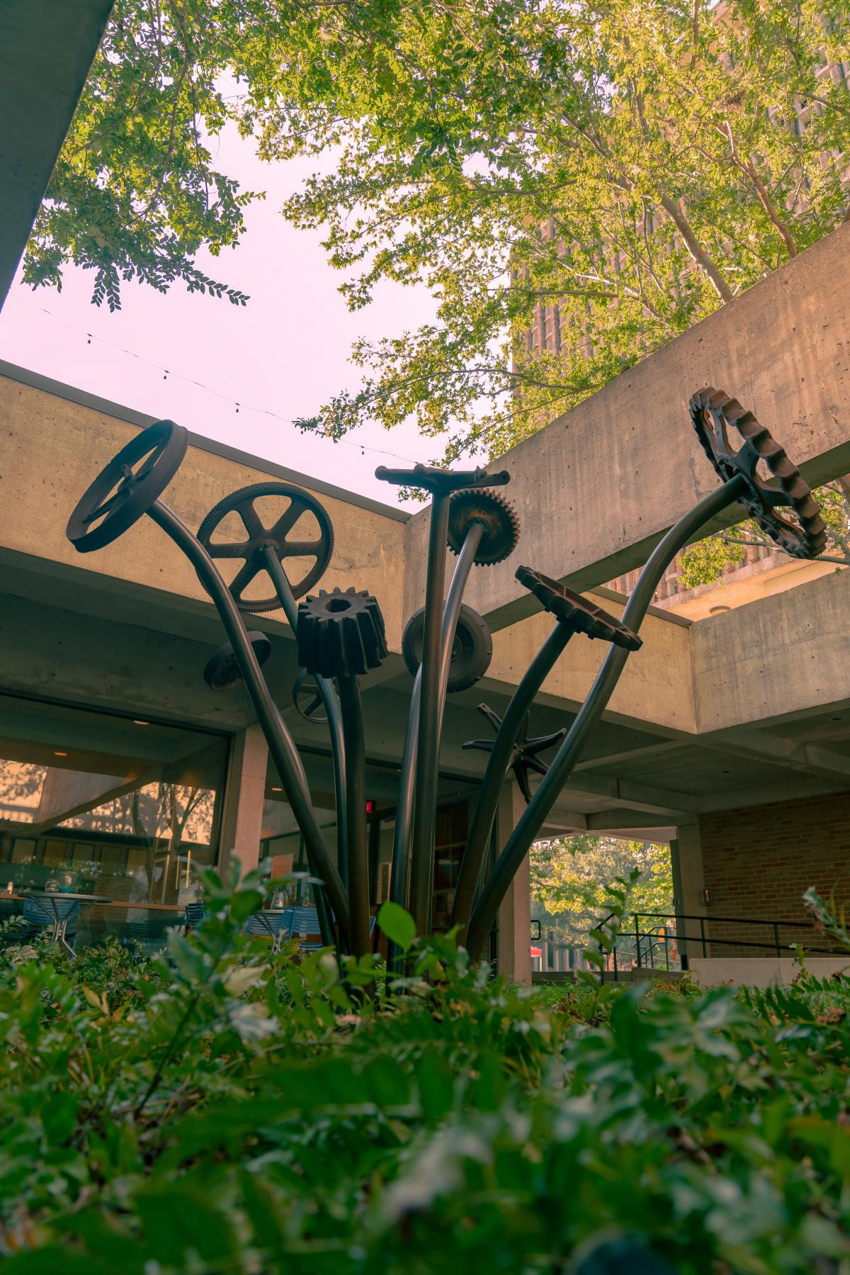 Unique sculpture of gears at the end of a long stem like a flower. This sculpture is a courtyard of Lovett Hall and is surrounded by greenery.
