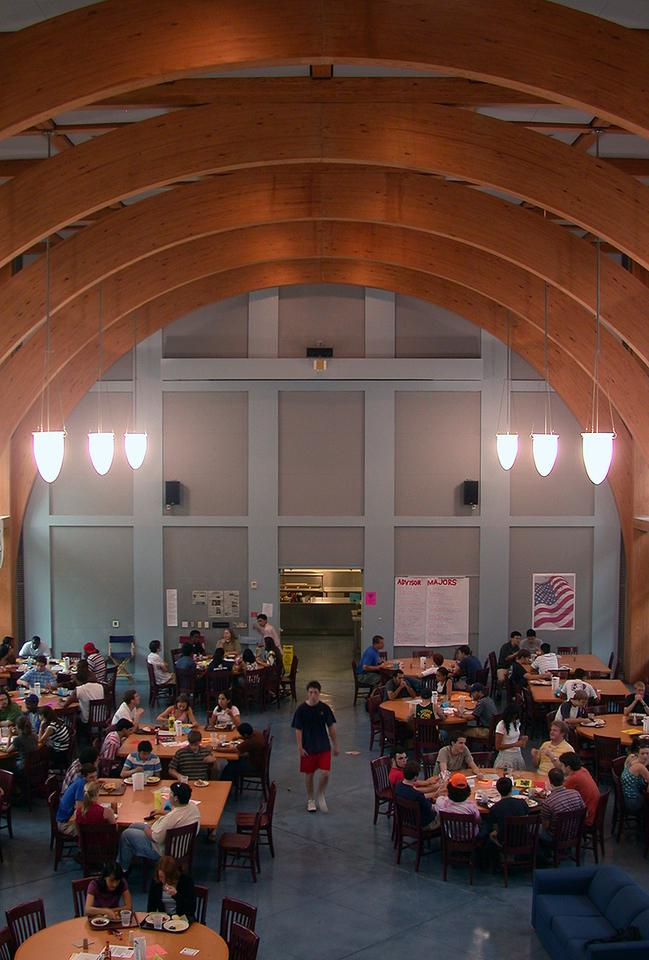 Inside view of Martel College commons, with students sitting at tables and chairs under a high arched ceiling.