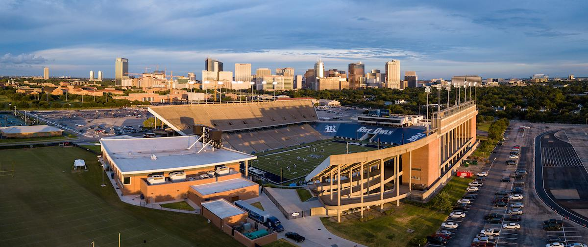 Aerial view of Rice Stadium with the Houston skyline in the background.