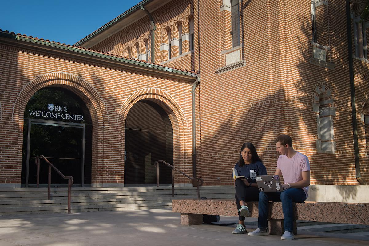 "Picture features two students sitting in front of Sewall Hall, with ""Rice Welcome Center"" on the glass of the door of the building"