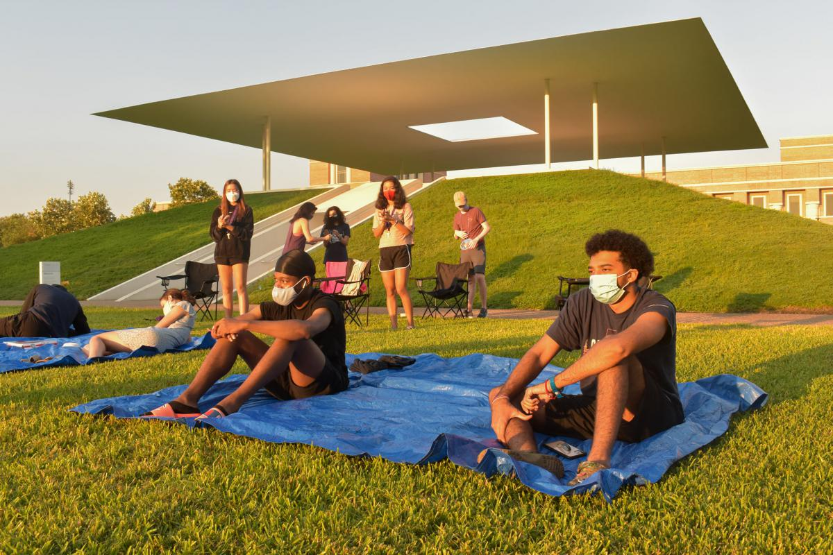 Students sit on tarps on the grass in front of the Skyspace, wearing masks and social distancing.