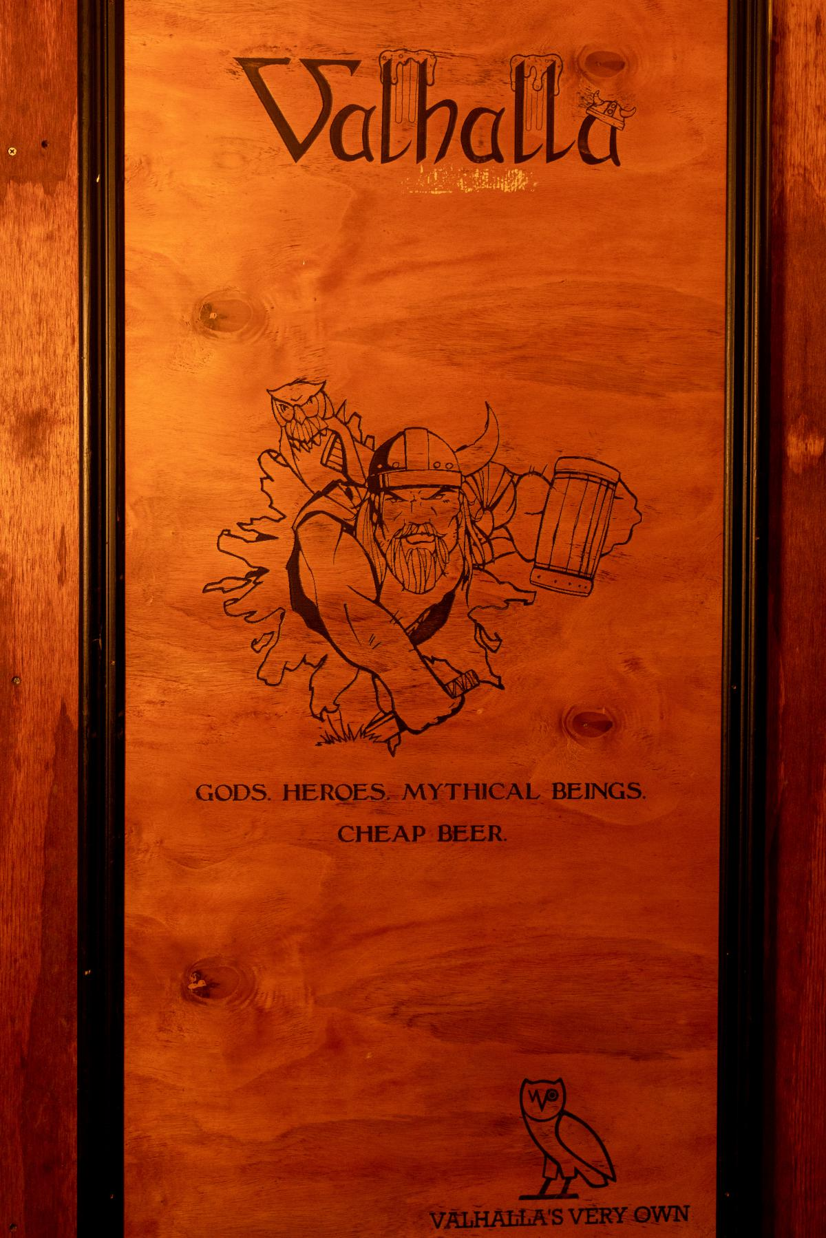 """Vertical picture of a drawing of a Viking inside the graduate student bar, Valhalla. The writing below the drawing says """"Gods, Heroes, Mythical Beings, Cheap Beer."""""""