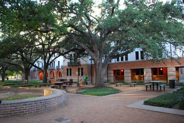 Courtyard outside of Will Rice College with picnic tables and benches as well as large trees.