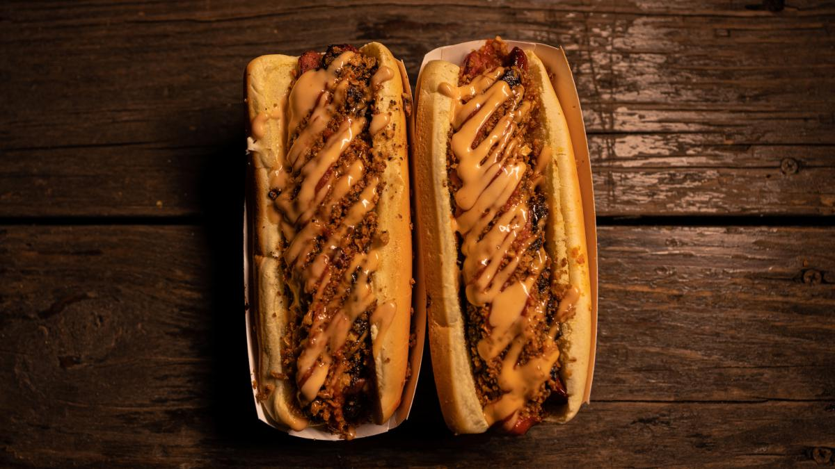 Picture taken from above of two hot dogs with chili and cheese on a brown table.