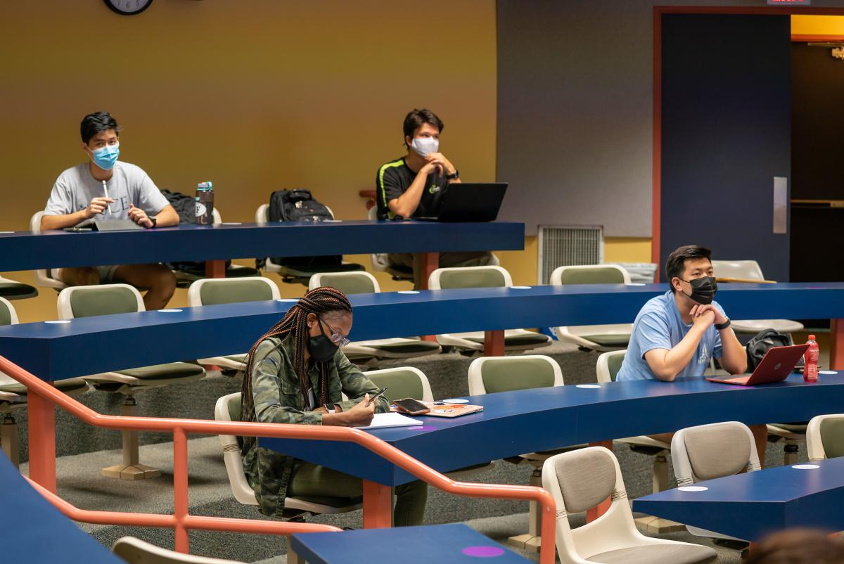 Students wearing masks sit apart in this lecture-hall style classroom with long tables.