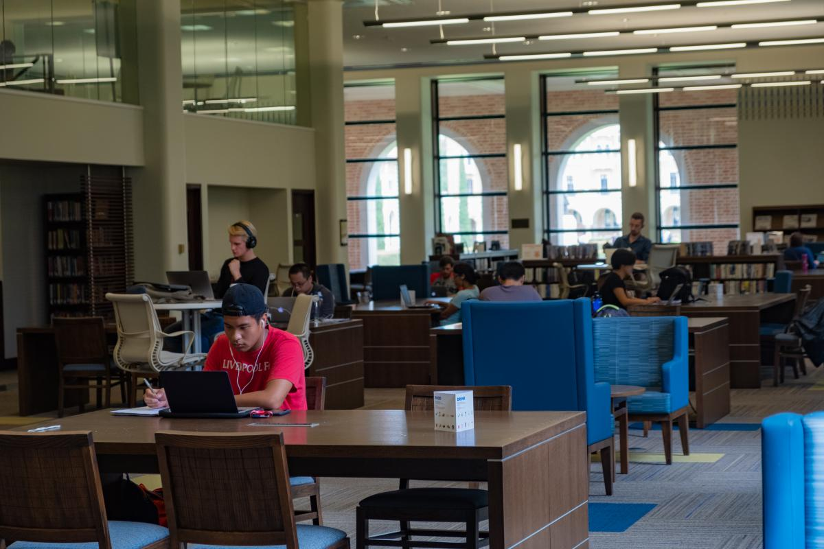 A large room inside the library with books, tables and chairs where students are sitting and working on laptops or reading books.