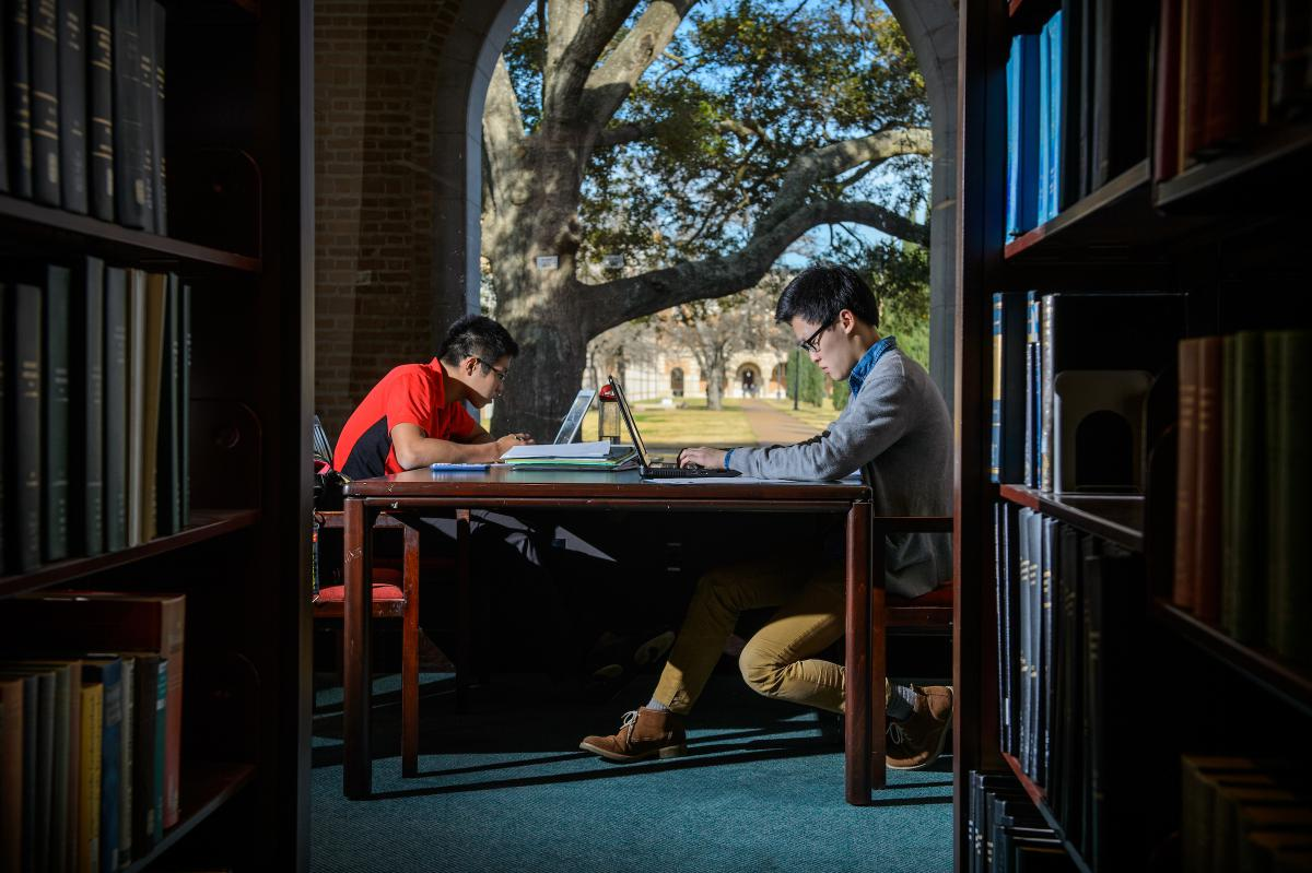 Picture taken from in between two bookshelves. At the end, you can see two students sitting across from each other at a table in front of a window.