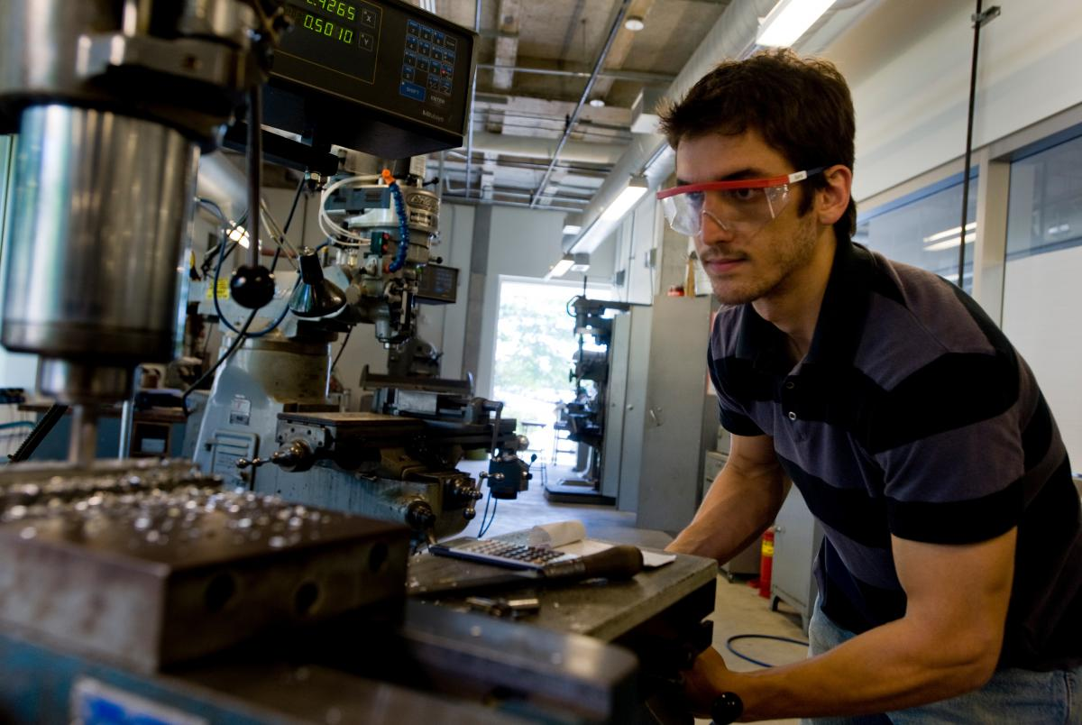 A student wearing protective eyewear is making something using the machinery in front of him.